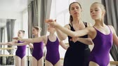 репетитор : Starting ballet dancers are practising arm movements during ballet class in studio. Tutor professional ballerina teaching them correcting positions and giving instructions