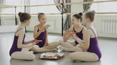 danseuse : Happy girls in bright leotards are eating pizza and talking while sitting on floor of ballet studio together. Tasty food, communication and children concept. Vidéos Libres De Droits