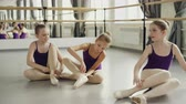 children ballet : Slim pretty children are wearing ballet slippers on studio floor and talking. Large mirror, ballet barre, bright bodysuits and beautiful interior are visible.