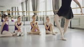 klassik : Ballet teacher professional ballerina is dancing on tiptoes demonstrating movements to her little students who are sitting on floor and watching tutor. Stock Footage