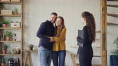 corretor : Friendly agent is giving keys to young couple buyers of new house, happy spouses are hugging and kissing, man is shaking hands with broker making deal.