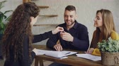 real estate sign : Young people are laughing and signing buy and sell contract then taking key and hugging during meeting with agent. Purchasing and selling property concept. Stock Footage