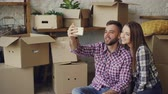 relocating : Happy young couple is making video call with smartphone after relocation. They are greeting friends, showing new house keys and boxes, chatting and smiling.