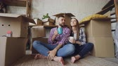 paketlenmiş : Young husband and wife are talking, looking around and kissing sitting on floor after moving to new house. Nice interior and many boxes with personal things are visible.