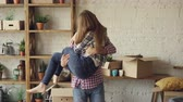 relocating : Happy strong man is whirling his wife and kissing her during relocation to new house after purchasing it. Romantic relationship, people and housing concept.