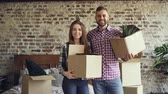 afetuoso : Portrait of happy young couple standing in new house, holding carton boxes, smiling and looking at camera. Family, relationship and relocation concept.