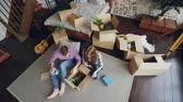 coisa : Top view of happy young couple unpacking things, opening box, taking things and talking after moving to new apartment. Relationship and relocation concept.