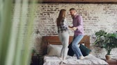 afetuoso : Young beautiful and loving couple is dancing on bed at home, careless people are having fun and laughing. Carelessness, free time and relationship concept.