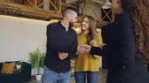 corretor : Slow motion of friendly agent giving keys to beautiful young couple buyers of new house, happy spouses are kissing and looking around with pleasure.
