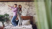привязчивый : Slow motion of young beautiful and loving couple dancing having fun and laughing in bed at home. Carelessness, free time and relationship concept. Стоковые видеозаписи