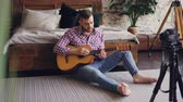 музыкант : Handsome man blogger and guitarist is recording video lesson about guitar using camera. Bearded guy is greeting his followers, talking and showing guitar parts.