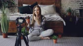 contar : Pretty girl popular blogger is recording video about house flowers with camera sitting on floor near double bed in nice bedroom. Girl is talking and holding plant.