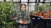 зелень : Portrait of adorable small girl in apron standing inside greenhouse, holding pot plant, smiling and laughing. Orcharding, people and childhood concept. Стоковые видеозаписи