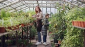 zahradník : Young entrepreneur greenhouse owner is watering plants in her hothouse while her cute little child is helping her. Family business and growing plants concept. Dostupné videozáznamy