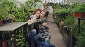 отношения : Young attractive worker of greenhouse and her cute emotional child are taking selfie hugging kissing and posing looking at smart phone camera. Стоковые видеозаписи