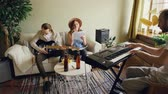бить : Amateur band is rehearsing in home studio singing and playing guitar and keyboard using microphone and musical equipment. Beer bottles and snacks are visible.