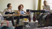 rehearsal : Charming female vocalist is singing looking at paper with lyrics while her handsome male friends are playing keyboard and guitar. Table with bottles and snacks is visible.