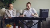 rehearsal : Young bearded keyboarder is adjusting musical instrument then playing looking at music sheet and talking to his friend guitarist who is sitting on sofa in studio. Stock Footage