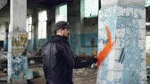 colunas : Bearded graffiti artist is painting on pillar in old abandoned building using aerosol paint. Modern youth subculture, creative people and street art concept.