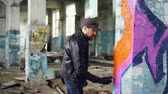 vandal : Handsome bearded guy graffiti artist is painting with spray paint inside abandoned building. Modern street art, youth subculture and creative people concept. Stock Footage