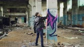 grafiti : Graffiti painter in casual clothing is drawing with spray paint on column in spacious abandoned building. Abstract images, modern art, creative people and hipsters concept. Dostupné videozáznamy