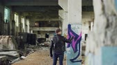 schmutzig : Male graffiti painter is creating abstract image with spray paint inside abandoned empty building. Old column is in foreground, dirty walls and windows in background.