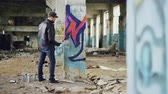vandal : Bearded young man is painting graffiti inside old industrial buliding using aerosol paint, he is making bright abstract image on column. Creativity and people concept. Stock Footage