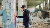 grafiti : Side view of graffiti artist bearded guy drawing on damaged column inside emply industrial building using bright aerosol paint. Creativity and people concept.