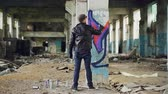 luvas : Back view of graffiti painter creating beautiful image with aerosol paint inside abandoned building. Artist is wearing blue jeans, black leather jacket, cap and gloves.