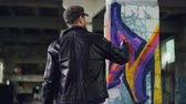 vandal : Rear view of male graffiti artist in leather jacket painting on damaged column inside empty industrial building. Young people, creativity, casual clothing and modern art concept.