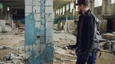vandal : Graffiti artist bearded guy is painting on pillar in abandoned building with bright aerosol paint spray. Pan shot of empty industrial building with dirty walls and broken windows. Stock Footage