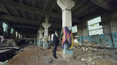 grafiti : Graffiti artist in protective mask is painting on high column in abandoned industrial building. Creative people, modern wall art and protective equipment concept.