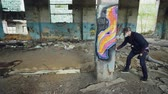 vandal : Pan shot of masked graffiti artist drawing abstract images on pillar in large empty building using paint spray. Painter is wearing casual clothing and protective gloves. Stock Footage