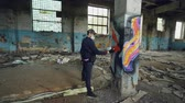 vandalisme : Male graffiti artist is decorating old damaged column inside empty industrial building with abstract pictures. Modern painter is using aerosol spray paint.
