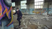 quadro : Urban street artist is decorating old pillar inside abandoned house with dirty walls and windows, he is using paint spray. Modern artwork and creative people concept. Stock Footage