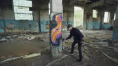 grafiti : Graffiti painter is protective mask and gloves is drawing on old column in dirty empty building using aerosol paint. Young man is wearing casual clothes and cap. Dostupné videozáznamy