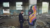 vandal : Pan shot of damaged abandoned building with high columns inside and male graffiti artist drawing abstract images on pillar. Man has protective gloves and gas mask. Stock Footage
