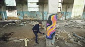 graffitis : High angle shot of young urban painter creating abstract image on column in old damaged building. Modern art, street artist, creativity and people concept.