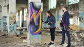 rehberlik : Urban painter is explaining to attractive young woman how to paint graffiti, they are standing beside pillar in damaged empty warehouse holding spray paint and talking. Stok Video