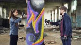 grafiti : Concentrated man and woman team of urban painters are painting graffiti on pillar inside ruined empty house using aerosol paint. Dirty interior in background. Dostupné videozáznamy