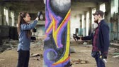 fantasia : Two skilled graffiti artists bearded guy and attractive young woman are working together in abandoned warehouse decorating old column with abstract image. Vídeos