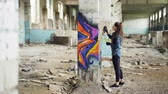 vandalisme : Pretty girl graffiti artist is decorating old damaged column inside empty industrial building with abstract pictures. Modern painter is using aerosol spray paint. Vidéos Libres De Droits