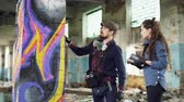 explicando : Attractive bearded guy graffiti artist is talking to his serious student pretty young woman and teaching her how to use aerosol paint decorating old building. Stock Footage