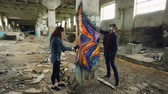 graffitis : Time-lapse of graffiti artists are using aerosol paint to decorate abandoned industrial building with modern graffiti images. Creativity, street art and people concept. Vidéos Libres De Droits