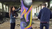 graffitis : Two serious graffiti painters are decorating empty industrial building with abstract images using bright aerosol paint. Creative teamwork, young people and art concept.