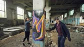 graffitis : Young people graffiti artists are using aerosol paint to decorate abandoned industrial building with modern graffiti images. Creativity, street art and people concept. Vidéos Libres De Droits