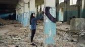 quadro : Urban artist is decorating column in abandoned warehouse with abstract image using aerosol paint. Girl is wearing casual clothing and listening to music with headphones. Stock Footage