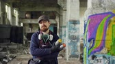 grafiti : Portrait of bearded guy graffiti painter standing in old empty building with graffiti painting in background and holding spray-paint. Man has gas mask and wearing gloves. Dostupné videozáznamy