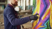grafiti : Bearded man graffiti painter is using aerosol paint to decorate pillar in old industrial building. Modern urban art, creative young people and hobby concept.