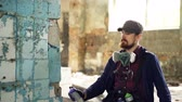 vandal : Serious bearded guy is concentrated on painting graffiti on old dirty column inside abandoned building with aerosol paint. Man is wearing casual clothes and gloves. Stock Footage